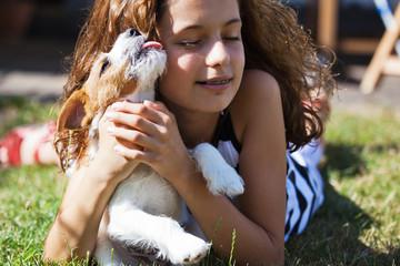 Parson Russell Terrier Welpe leckt Mädchen im Gesicht