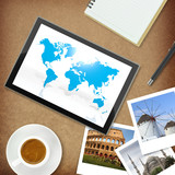 Tablet computer with world map and photos of famous places