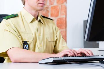 Polizist am Schreibtisch im Revier