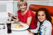Little girl enjoying dinner with her mom