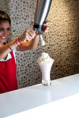 Attractive girl pouring shake in glass