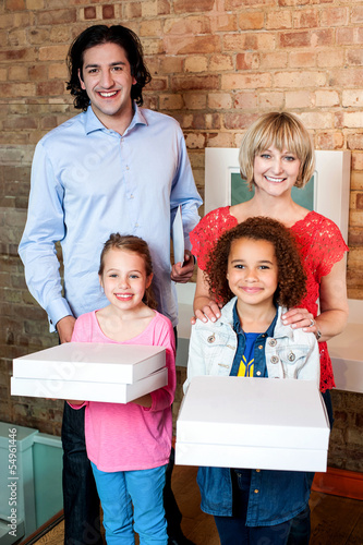 Excited little girls holding pizza boxes