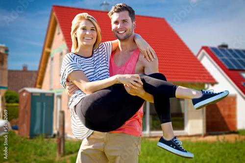 Junges Paar vor dem neuen Eigenheim