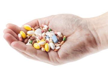 Man's hand holding a handful of medicine pills