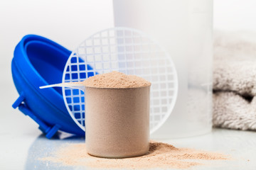 Scoop of chocolate whey isolate protein in front of shaker