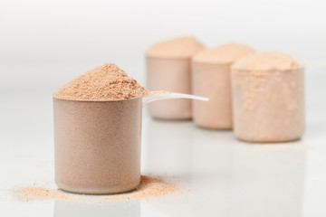 Scoop of chocolate whey isolate protein in front of three scoops