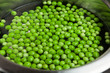 Green peas thawed and cooking in the water in the metal pot