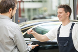 Auto mechanic and customer. Cheerful auto mechanic giving a car