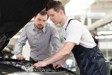 Examining a car. Confident auto mechanic examining car engine wh