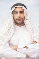 Arab businessman. Confident Arab businessman holding his arms cr