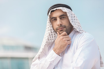 Thoughtful Arab businessman. Confident Arab businessman holding