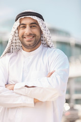 Cheerful Arab businessman. Smiling Arab businessman holding his