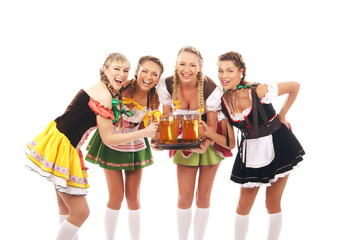 Four young women in Bavarian clothes holding glasses of beer