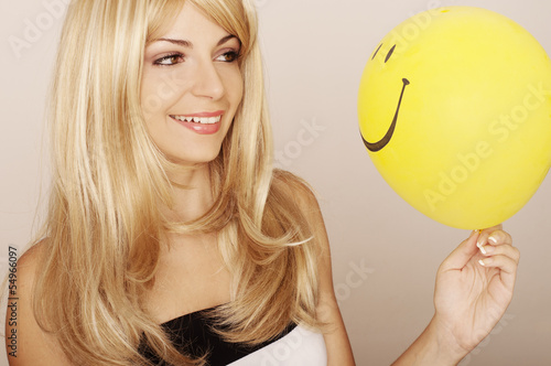 Girl holding smiley face balloon Poster