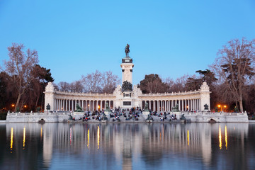 Tourists sit near monument to Alfonso XII at pond in Retiro Park