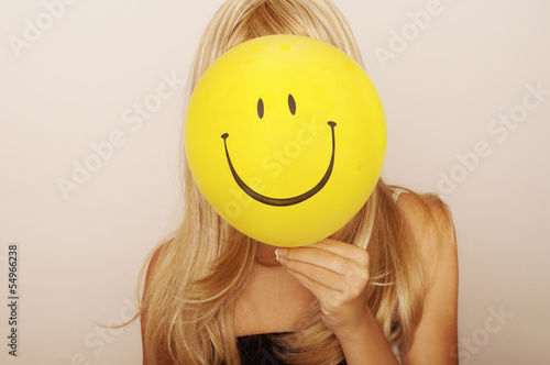 Girl holding smiley face balloon in front of her