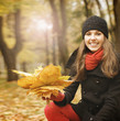 A lovely brunette woman holding leaves in an autumn park