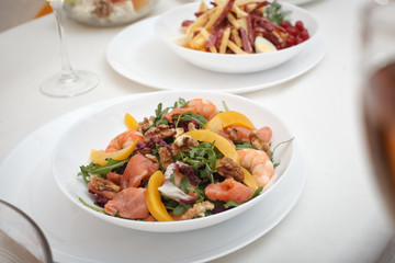 Fresh mixed salad with nuts, shrimps, salmon and peaches close