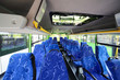 Rows of soft blue seats inside saloon of empty city bus