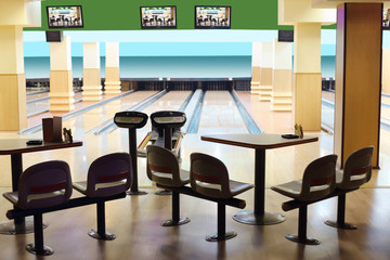 Small light bowling with hanging displays, table and chairs.