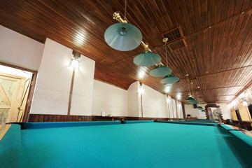 Several of billiard tables with green cloth and round lamps