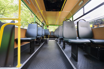 Rows of grey seats inside clear saloon of empty city bus