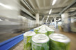 Many green cans with drinks go on conveyor