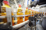 Yellow plastic bottles with light beer go on conveyor belt