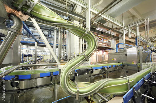 Green cans move fast on conveyor in factory