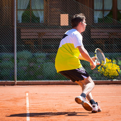 tennis player moving backwards to reach the ball