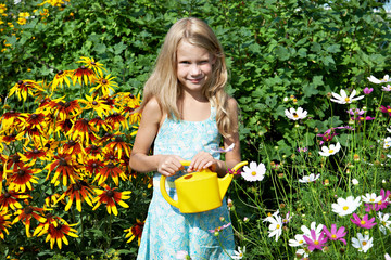 Little girl with watering can near flowers