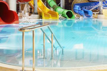Metal railings, pool and multi-colored water slides