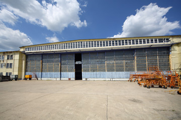 Big old battered aircraft hanger with big gate at sunny day