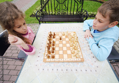 Little frowning girl and smiling boy play chess at table in park