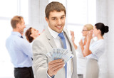 happy businessman with cash money in office