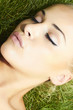 Beautiful blond girl sleeping on green grass. beauty woman.