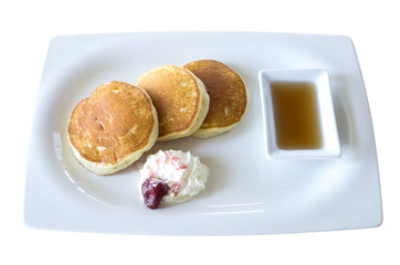 buttermilk pancakes with maple syrup and weep cream in plate on