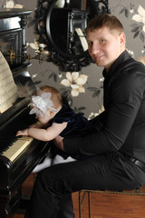 Smiling man in black with cute baby sits at piano in room. Baby