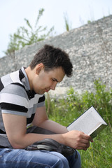 Young brunet man in jeans intently reads book outdoor at summer