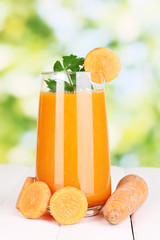 Glass of carrot juice on wooden table, on green background