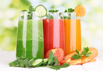Fresh vegetable juices on wooden table, on green background