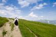 Weibliche Wanderin auf einem Weg an einer Wiese