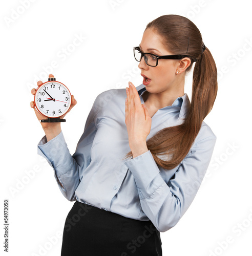 Surprised woman holding an alarm clock in a hand