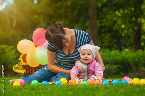 Keuken foto achterwand Picknick cute baby and mom are playing on the green grass