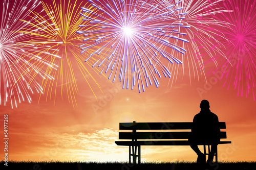 man watching the fireworks on the bench