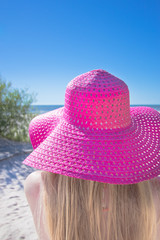 Young woman with big pink hat on the beach