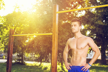 Attractive guy working out outdoors on a sunny summer day