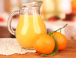 Full jug of orange juice, on wooden table on bright background