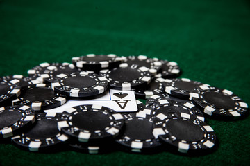 Ace of spades in pile of black poker chips