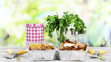 Food in boxes of foil on wooden table on nature background